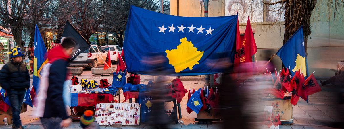 Des personnes passent devant des drapeaux du Kosovo installés dans la capitale, Pristina, le 16 février 2018.